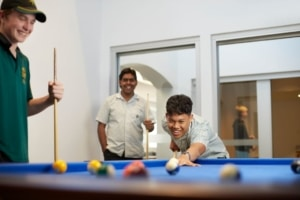 Photo of three boarding school students playing a game of pool in their recreation area