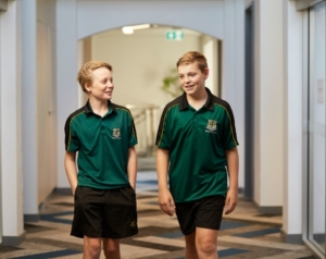 Two junior school boarding student walk down a hall together smiling