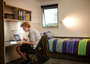 Boarding school student sitting at desk in front of laptop with pen and paper out to take notes