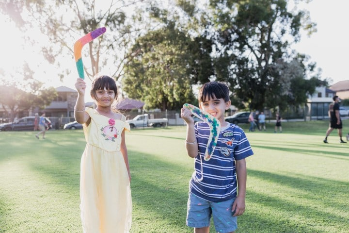 Photo of two young children holding boomerangs at Wesley College at the Moorditj by Moonlight event